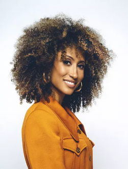 Portrait of Elaine Welteroth, an African American woman with big curly hair, wearing a golden tan jacket and smiling.